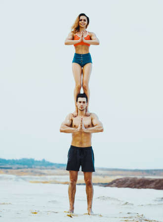 Young sports couple doing acroyoga exercises on sand beach. Bright white colors. Stock Photo