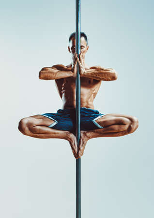 Young strong man pole dancing on blue and white background Stock Photo