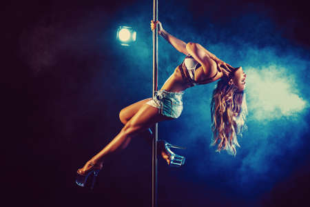 Young slim woman pole dancing in dark interior with lights and smoke