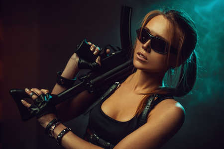 Young strong cool woman with big gun and sunglasses in dark dramatic urban interior