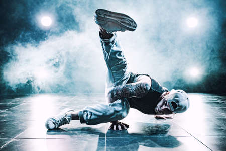 Young man break dancing in club with lights and smoke. Tattoo on body. Blue tint colors. Stock Photo