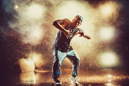 Young cool man break dancing in club with lights, smoke and water. Tattoo on body. Stock Photo