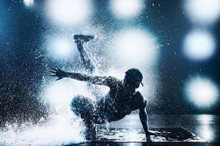 Breakdance des jungen Mannes im Verein mit Lichtern und Wasser. Tätowierung am Körper. Blautönung Farben. Standard-Bild
