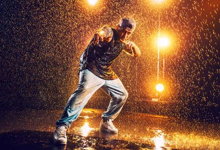 De danser van de jonge mensenonderbreking die zich in club met lichten en water bevindt. Tatoeage op lichaam.