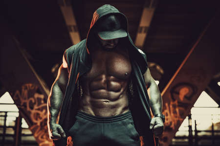 Young strong man bodybuilder with informal style clothing with hood standing in urban city interior. Dark red colors.