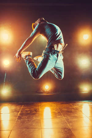 Young man break dancing in club with lights and smoke. Warm colors.