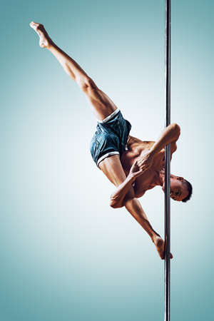 Young strong man pole dancing on blue and white background Stockfoto