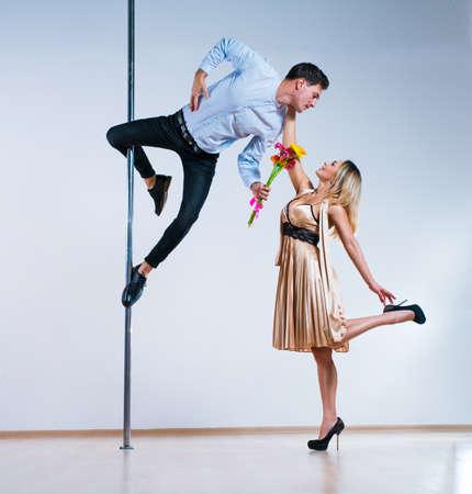 Jonge man en vrouw paaldansers. Man die bloemen geeft aan vrouw. Liefde concept. Stockfoto
