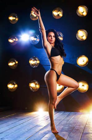 Young sexy sports woman standing on wall background with lights