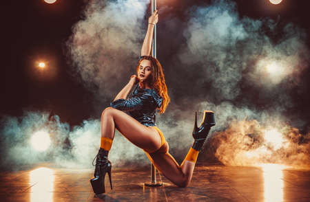 Young sexy slim woman pole dancing in dark interior with lights and smoke Standard-Bild - 96758442