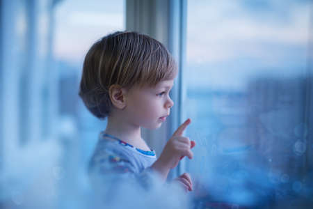 Cute two year child looking at window to the city. Soft blue romantic tint.