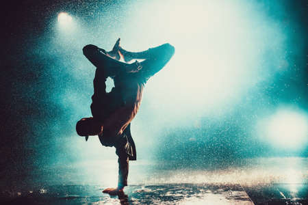 Young man break dancing in club with lights and water. Blue dramatic colors.