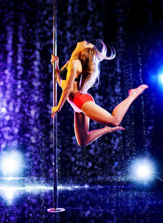 Young sexy slim woman pole dancing in dark interior with lights and water rain