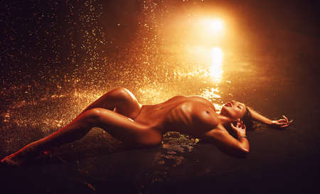 Young woman posing with water drops. Red vibrant light. Imagens
