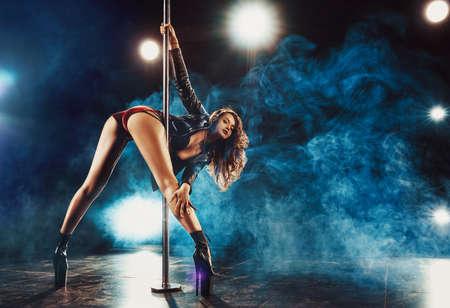 Junge schlanke Frau Pole Dance im dunklen Innenraum mit Lichtern und Rauch Standard-Bild