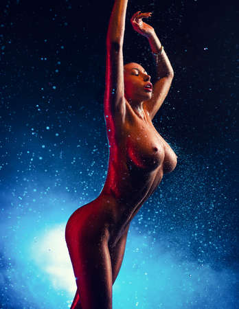 Young sexy nude woman posing with water drops. Blue vibrant light. Stock Photo