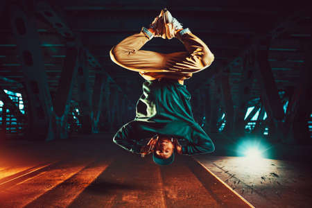 Young cool man break dancer jumping upside down. Urban bridge with cool and warm lights background.