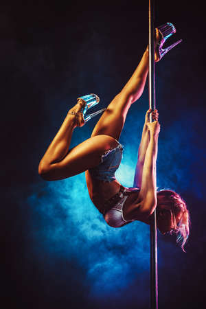 Young sexy slim woman pole dancing in dark interior with smoke
