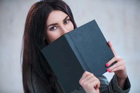Young business woman with book portrait on gray wall background