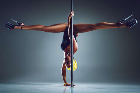 Young slim sexy woman pole dancing on gray wall background