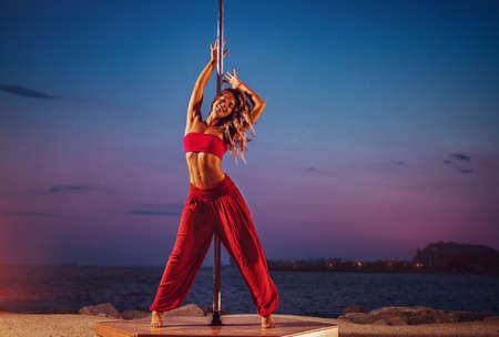 Young woman pole dancing on sea and sky background at twilight