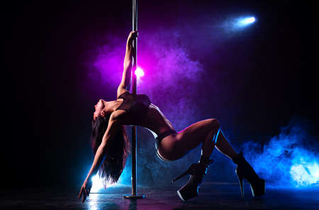 Young slim brunette woman pole dancing in dark interior with smoke and lights