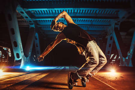 Young cool man break dancer on urban bridge with cool and warm lights background. Tattoo on body. Stok Fotoğraf