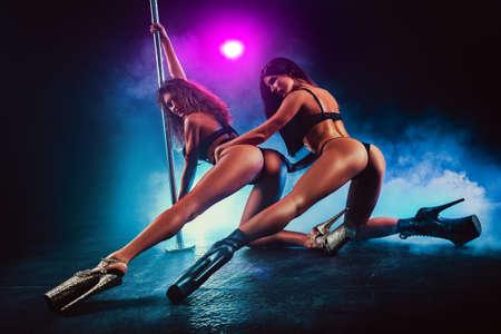 Squadra di due donne pole dancing in interni scuri con fumo e luci colorate. Archivio Fotografico