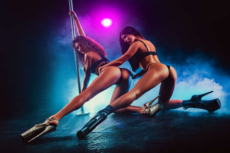 Two sexy pole dancing women team in dark interior with smoke and colored lights. Archivio Fotografico