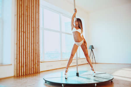Young sexy pole dancing woman in lingerie standing bright white interior Stok Fotoğraf