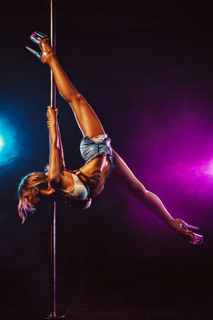 Young sexy slim blond woman pole dancing in dark interior with smoke and light flares Stok Fotoğraf