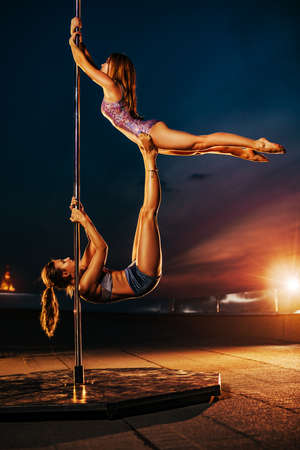 Young women pole dancing on roof. Twilight sky dramatic background.