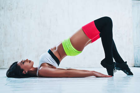 Young slim brunette fitness woman stretching on white wall background