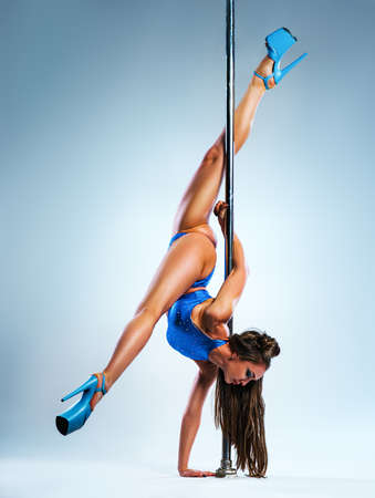 Young slim sexy brunette woman in blue clothing pole dancing on bright white and blue background Stok Fotoğraf