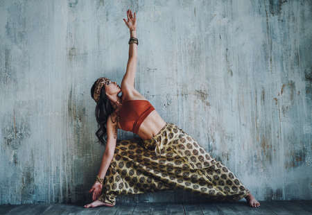 Young beautiful yogi woman in traditional clothing stretching on wall background Stok Fotoğraf