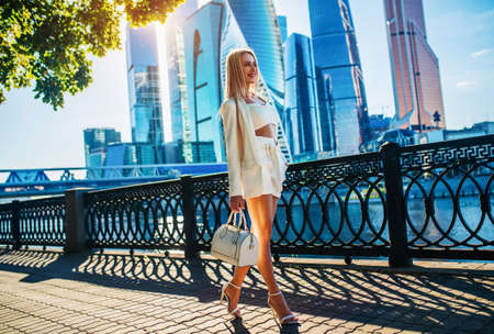 Young fashion business woman walking along river. Modern skyscrapers on background. Stok Fotoğraf
