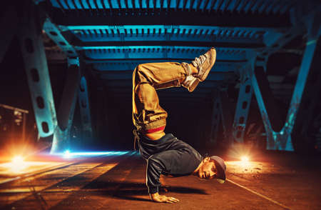 Young cool man break dancer standing on hands upside down. Urban bridge with cool and warm lights background.