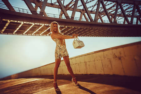 Young fashion woman with bag standing under bridge. Warm sunset light. Stok Fotoğraf