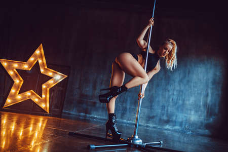 Young sexy pole dancing woman standing in dark stone interior with star lights shape