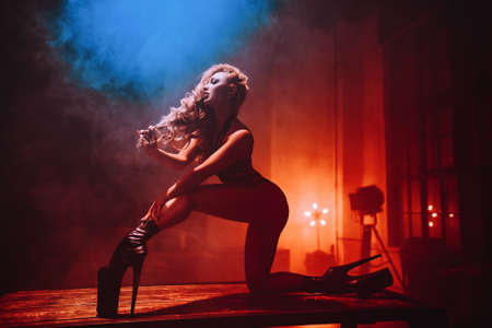 Young slim sexy blond woman dancing on table in hall interior with smoke and lights