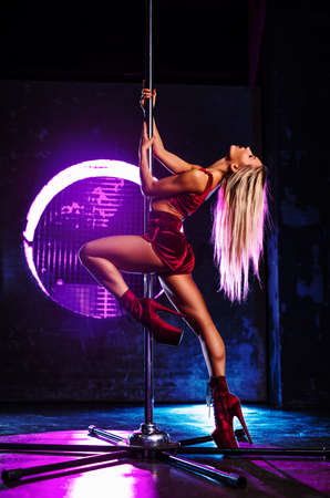 Young sexy slim blond woman pole dancing in dark interior with pink and blue lights