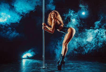 Young slim blond woman pole dancing in dark interior with smoke and lights