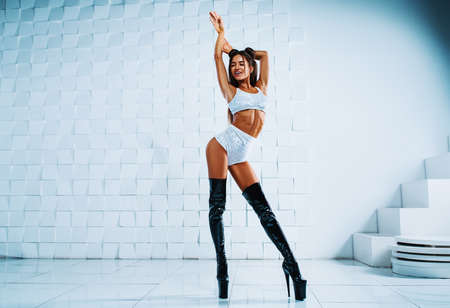 Young slim sexy brunette woman in white clothing and black leather boots standing in white interior Stok Fotoğraf