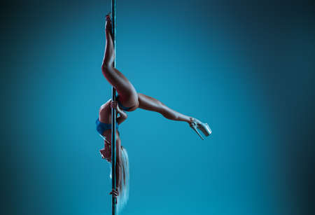 Young slim blond woman pole dancing upside down on wall background. Cold blue tint.