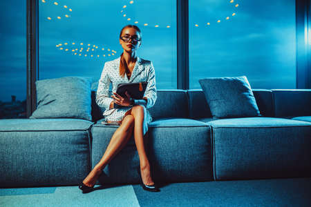 Young business woman with glasses and folder sitting in modern office interior with big windows. Lights reflection on background.