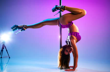 Young slim sexy woman pole dancing on vibrant pink and blue background