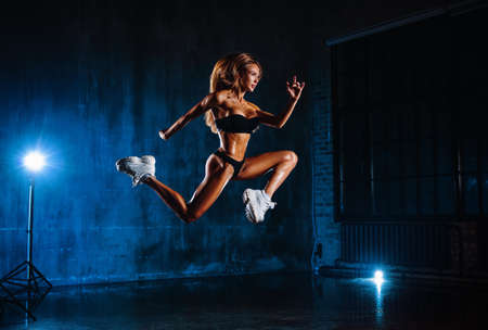 Young fitness woman jumping high in dark interior with blue lights