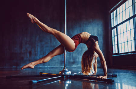 Young sexy pole dancing woman standing in dark stone interior with big windows Stok Fotoğraf