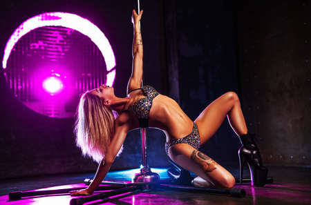 Young sexy slim blond woman pole dancing in dark interior with pink and blue lights. Tattoo on body.