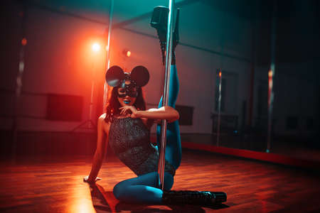 Young sexy woman in mouse mask pole dancing in room with mirrors and warm and cold lights